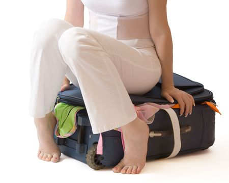 Barefooted woman sitting on a suitcase crammed full of clothes, isolated, with clipping path