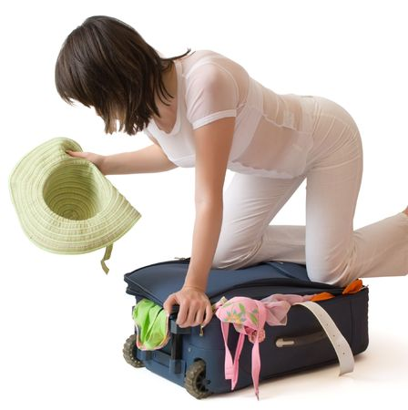 Young woman standing on a suitcase crammed full of clothes isolated over white  Stock Photo