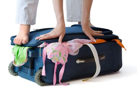 Barefooted woman standing on a suitcase crammed full of clothes, isolated, with clipping path photo
