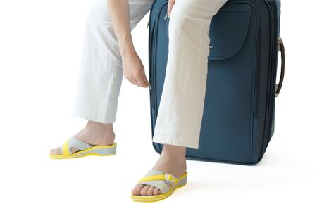 Female sitting on a  suitcase and zipping or unzipping it photo