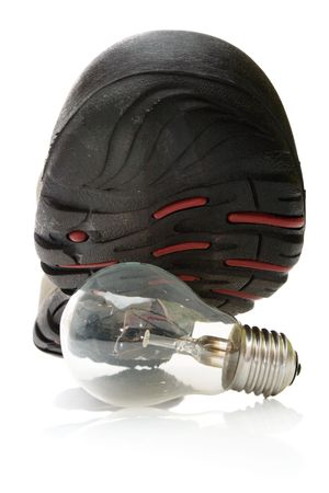 Man shoe steeping and crushing the electric light bulb, isolated, with clipping path, over white photo
