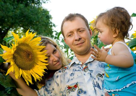 Happy family - mom, dad and  in sunflower field Stock Photo - 3391010