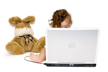 girl working with laptop, toy bunny near her, isolated, on white background Stock Photo - 3447834
