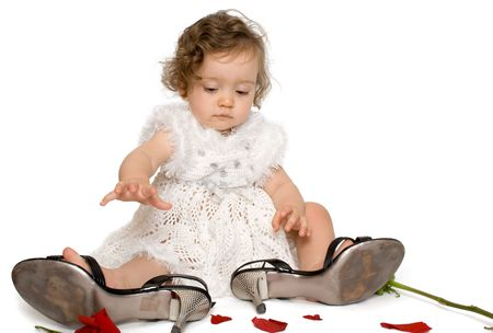 girl sitting  in mom's shoes, with rose petals on the floor, isolated, on white background photo