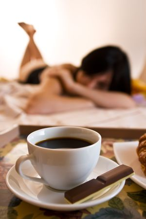 Coffee cup, a bar of chocolate for a girlfriend on bed, with shallow focus photo