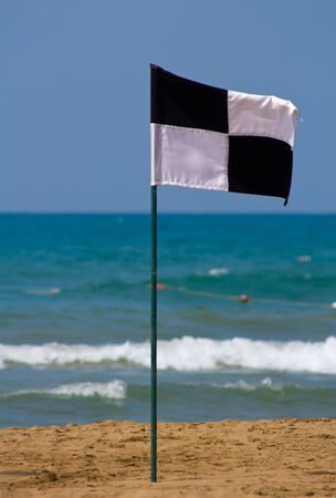 zoned: Quartered black and white flag on the beach, showing zoned off area Stock Photo