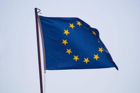 flagpoles: European Union flag across the blue sky