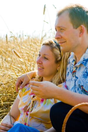 Attractive loving couple having picnic at the sunny day in the wheat field photo