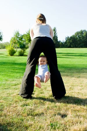 Mother swinging  little baby on the grass meadow photo