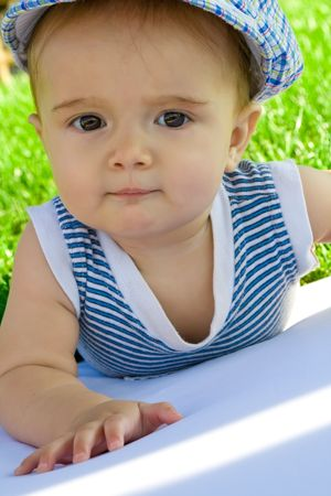 Baby in cap and striped shirt, lying on the grass, shot close up Stock Photo - 3500084