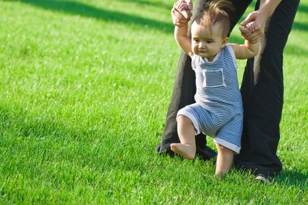 Baby girl stepping on the green grass, mother hands holding her Stock Photo