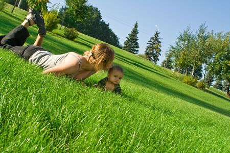 Mother kissing baby, lying on the grass photo