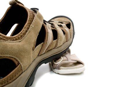 adult shoe stepping on  sandal, isolated, on white background photo