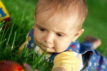 Baby lying in the grass watching or examining something photo