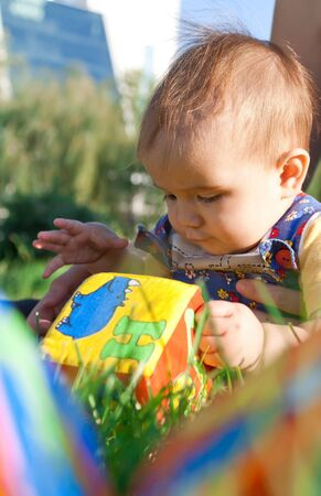 soft tissue: Baby lying in the grass and playing with soft tissue blocks  Stock Photo