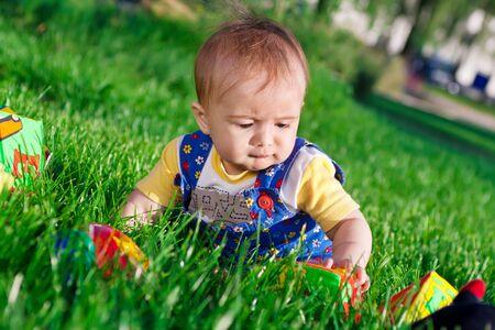 Baby girl in the grass examining blocks photo