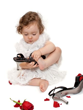 Baby girl trying on mom's shoes, with rose petals on the floor, isolated