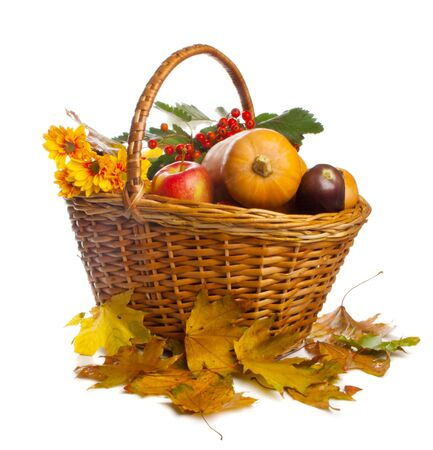 Wicker basket with autumn fruit and vegetables, isolated photo