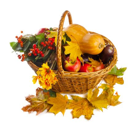 Wicker basket with autumn fruit and vegetables, shot from top, isolated photo