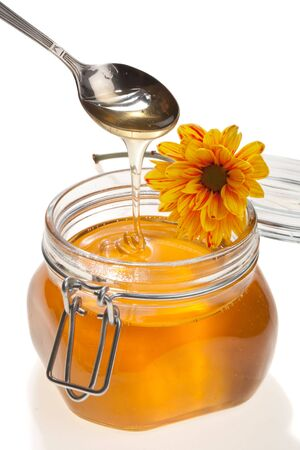 curative: Honey jar, with a yellow-and-red flower on it, isolated