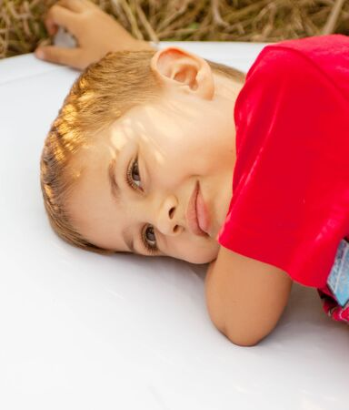 A dreaming boy, lying on a white picnic mat photo
