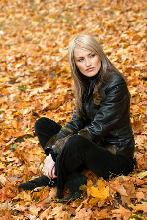 Blond girl sitting in yellow autumn leaves  photo