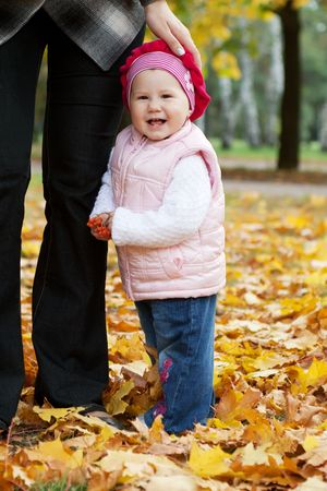 Little girl standing near mother in autumn park  photo