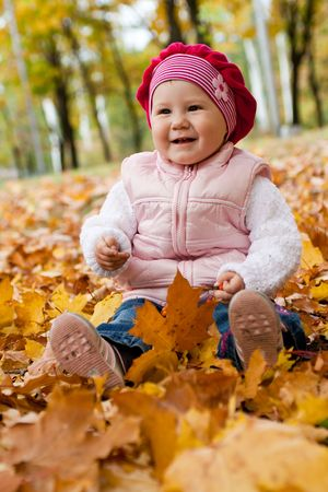 Smiley girl sitting on yellow rug made of maple leaves Stock Photo - 3715699