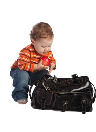 Kid with red apple, sitting near big black bag, isolated photo