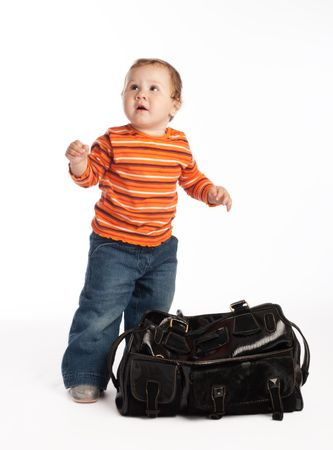 little kid standing beside big female bag photo