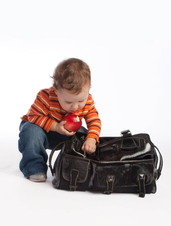 Kid with red apple unzips female bag photo