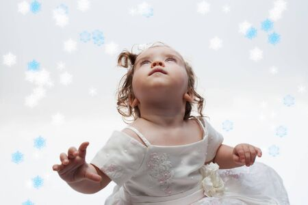 interested baby: Cute little girl looking up at snowflakes