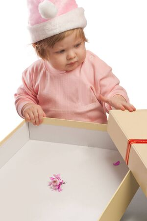 Serious kid in pink Santa hat looks at empty present box Stock Photo - 3873340