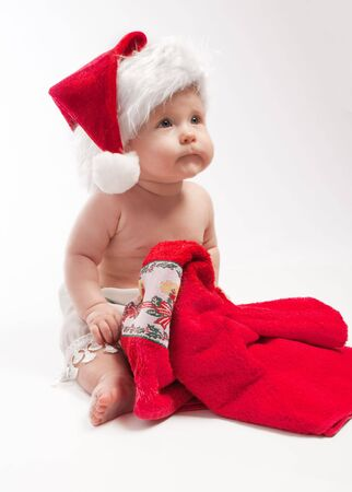 Baby in red Xmas hat looks up Stock Photo - 3873342