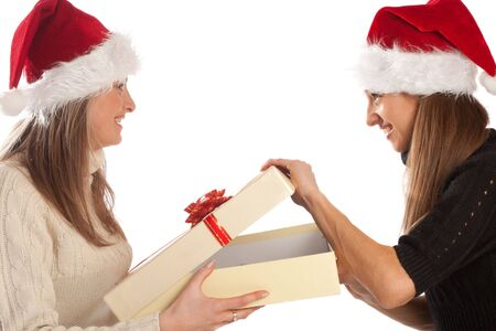 Pretty girl in Santa hat opening Xmas present from her friend, isolated photo