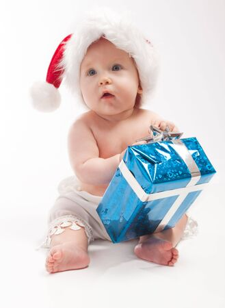 Baby in red Xmas  sits with blue present box photo