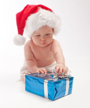 Baby in Santa hat playing with blue present box photo