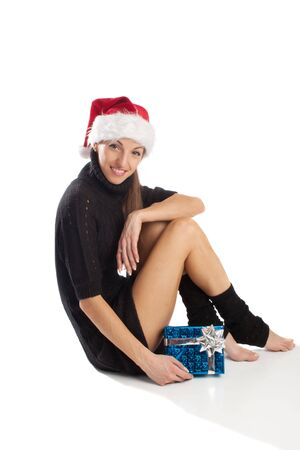 Pretty woman in Santa hat sitting with present box, isolated photo
