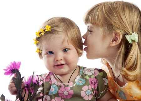 Cute red-haired girl whispering something to her sister, isolated photo