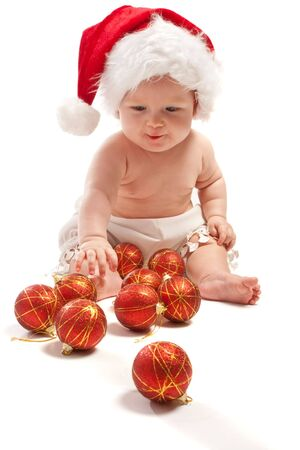 Baby in Santa hat playing with Christmas balls, isolated photo