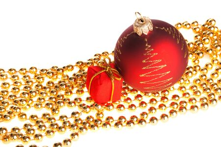 Xmas ball and present box lying on yellow beads, isolated photo