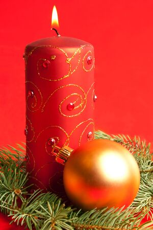 Red burning candle with golden xmas ball lying on fir-tree branch photo
