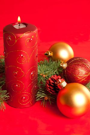 Christmas decoration: candle and three xmas balls on red background photo