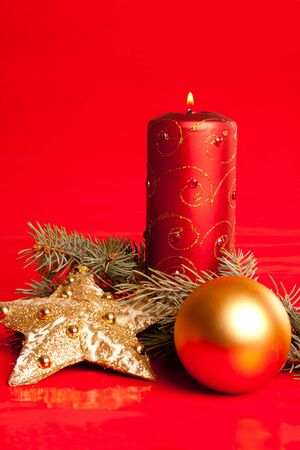 Burning candle, star and ball on red background photo