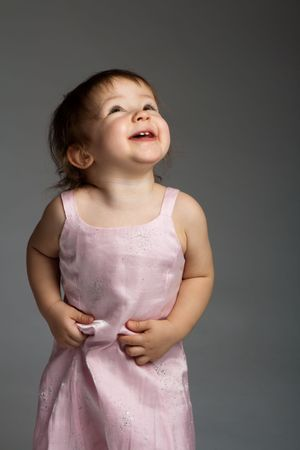 Lovely laughing toddler looking up on grey background photo