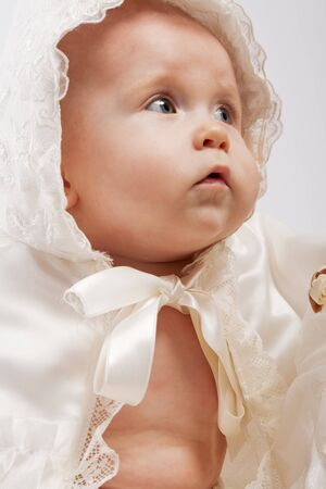 baptism: Baby in abiti di seta bianca battesimale
