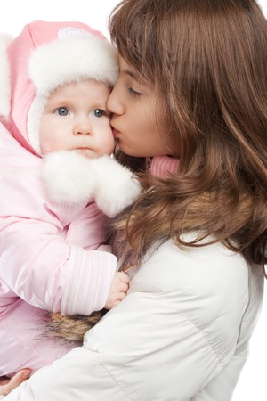 Elder sister kissing baby girl in winter clothes, isolated photo