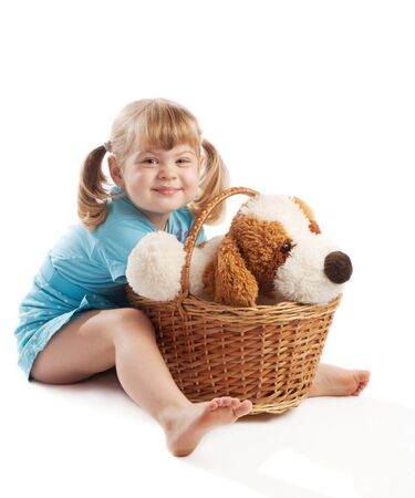 Little girl sitting  near basket with puppy toy photo