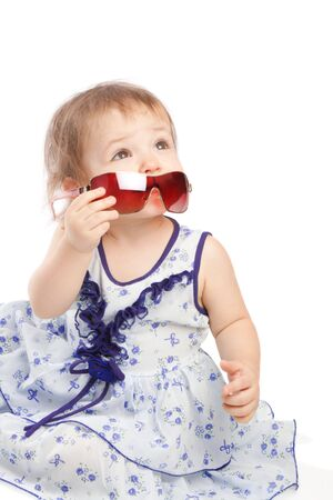 Little girl taking off adult sunglasses, isolated photo
