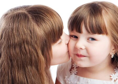 Little girl kissing her sister, isolated Stock Photo - 4022586